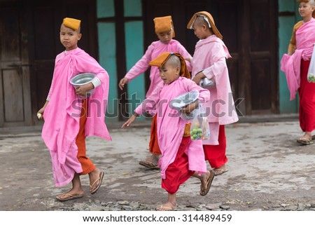 MANDALAY,MYANMAR,JANUARY 17, 2015 : A group of young Buddhist nuns is walking in the streets of Mandalay, Myanmar (Burma). - stock photo