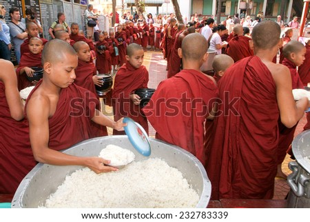 Mandalay, Myanmar, 17 January 2010: Monks in a row at Mahagandayon Monastery. Monks are venerated members of Burmese society. In these image they are going to lunch. - stock photo