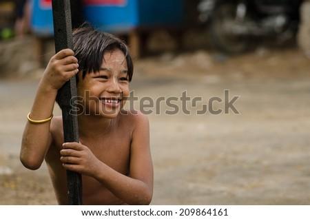 MANDALAY,MYANMAR-MA Y 10:Unidentified Myanmar kid smiles after the rain on May 10,2014 in Mandalay,Myanmar. - stock photo