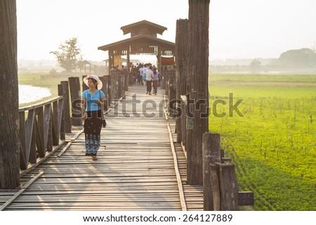 Mandalay, Myanmar- MAR 5: Unidentified Myanmar People on U-Bein bridge in sunset in Mandalay, Myanmar on March 5 2015. The U-Bein bridge is the longest teak bridge in the world, 1.2km length. - stock photo