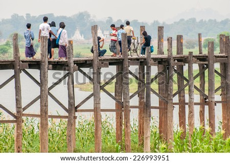 Mandalay, Myanmar - March 15,2011: Myanmar people on U Bein Bridge in Mandalay of Myanmar.U Bein Bridge is the oldest and longest teak wooden bridge in the world. - stock photo