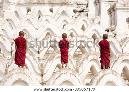 MANDALAY, MYANMAR - MARCH 12: Three monks standing at Hsinbyume pagoda temple pagoda temple on March 12, 2016 in Mandalay, Myanmar. - stock photo