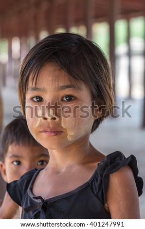 MANDALAY, MYANMAR - MARCH 10 : Unidentified Burmese girl with traditional thanaka on her face on March 10, 2016 in Mandalay, Myanmar.Thanaka is a yellowish-white cosmetic paste made from ground bark