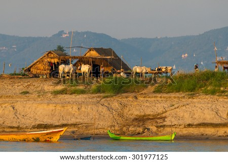 Mandalay, Myanmar - November 19:  Farmers at a bank of Irrawaddy River prepare for their daily work in the early morning sun. November 19, 2015 in Mandalay, Myanmar - stock photo