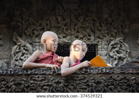 MANDALAY, MYANMAR - NOVEMBER 25 : Little young Buddhism novices are reading textbook after class in temple on November 25, 2015 in Mandalay,Myanmar  - stock photo
