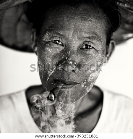 MANDALAY - MYANMAR - NOVEMBER 13, 2015: Unidentified Burmese woman with cigar and traditional hat on November 13, 2015 in Mandalay, Myanmar. - stock photo