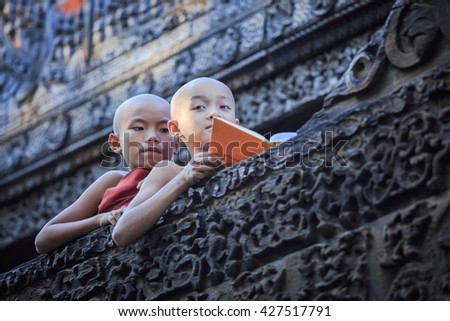MANDALAY, MYANMAR - NOVEMBER 25,2015 : Unidentified young Buddhism novices are reading textbook after class at Shwenandaw Kyaung Temple or Golden Palace Monastery. - stock photo