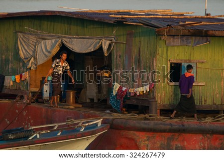 Mandalay, Myanmar - November 19:  Workers living at a cargo ship in the Irrawaddy River prepare for their daily work in the early morning sun. November 19, 2015 in Mandalay, Myanmar - stock photo