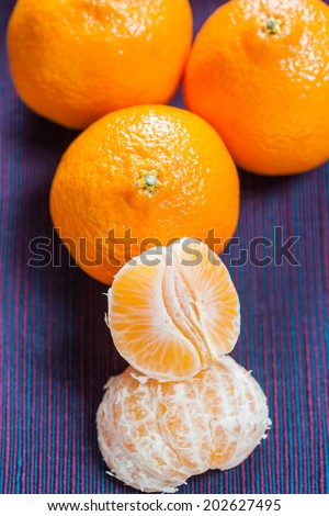 Mandarin orange segments with three whole mandarins in the background on a colorful cloth - stock photo