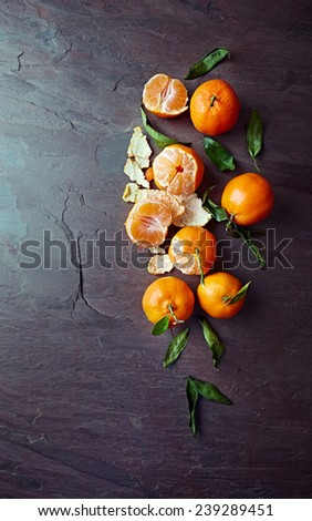 Mandarin oranges on a slate surface - stock photo