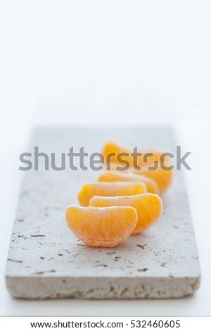 Mandarin wedges and skin on natural stone board and white background