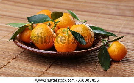 Mandarin with leaves on a plate. - stock photo