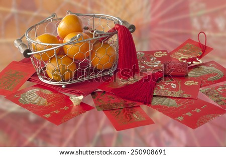 Mandarins in basket and red envelopes with good luck wishes on blurred background - stock photo