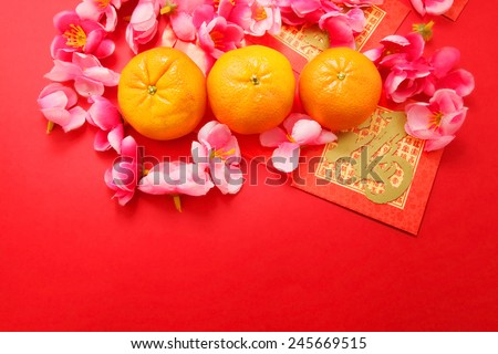"""Mandarins with Red Packets (with the character """"fu"""" meaning fortune) and Plum flowers on red background - stock photo"""