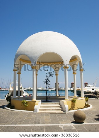 Mandraki harbor embankment pavilion with decorative iron tree and bird inside. Rhodes, Greece.