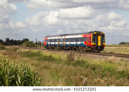 MANEA, UK - SEPTEMBER 25: An East Midlands operated class 158 diesel unit passes through Manea with a fast passenger service on route to the fenland city of Ely on September 25, 2015 in Manea