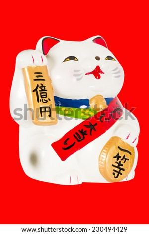 Maneki-neko - Japanese beckoning cat isolated on a red background. Traditional good luck charm. - stock photo