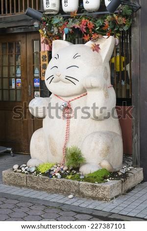 Maneki-neko - Large beckoning cat in front a store in Matsumoto, Nagano, Japan.  - stock photo