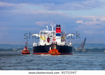 Maneuvers at sea on a cloudy day - Escorting tanker by tugs. - stock photo