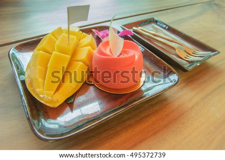 Mango and cake on wooden table.