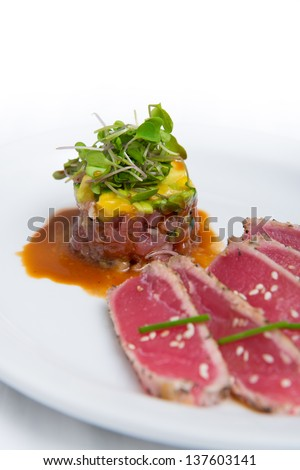 Mango avocado tuna tartare served with seared tuna sashimi isolated over white background - stock photo