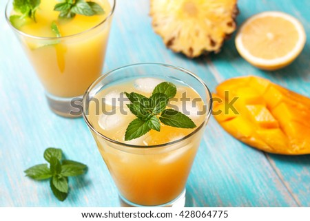 mango ice tea with mint in a glass  on  blue  wooden background - stock photo