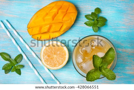 mango ice tea with mint in a glass  on  blue  wooden background (Top view ) - stock photo