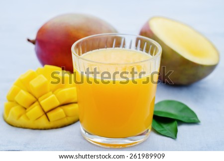 mango juice and fresh mango on a blue background. tinting. selective focus