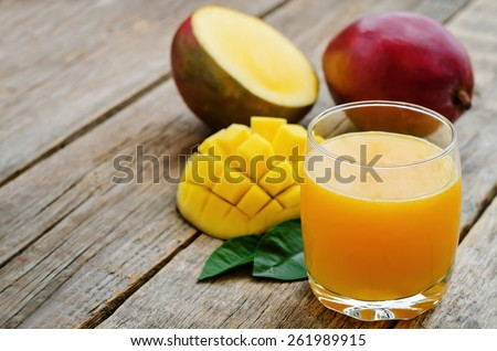 mango juice and fresh mango on a dark wood background. tinting. selective focus - stock photo