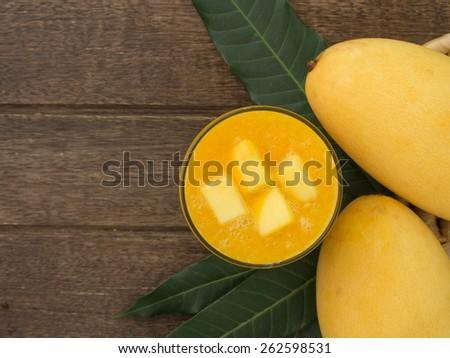 mango juice and mango on wood table. view above - stock photo