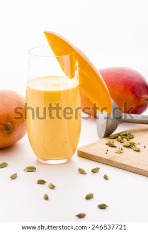 Mango milk shake in a glass decorated with a cut fruit chip. Crushed cardamon seeds on a wooden cutting board. A metal pestle and two entire mangos. Closeup. Selective focus. White background.  - stock photo