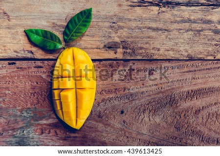 mango on a dark wood background. tinting. selective focus on the mangoes slices - stock photo