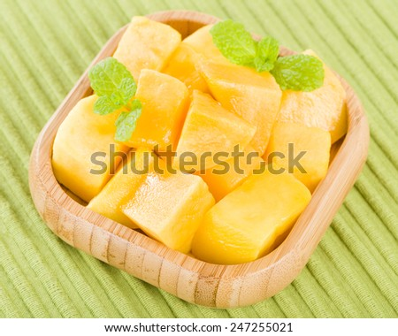 Mango - Pieces of mango in a square bamboo bowl on a green background. - stock photo
