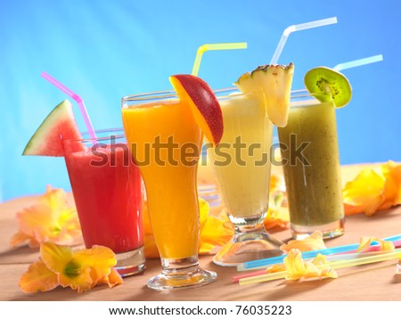 Mango, pineapple, watermelon and kiwi smoothie with drinking straws surrounded by gladiolus flower on wood (Selective Focus, Focus on the mango smoothie in the front) - stock photo