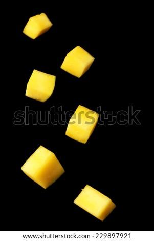 Mango slices on black background - stock photo