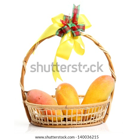 mangoes in wicker basket with yellow ribbon