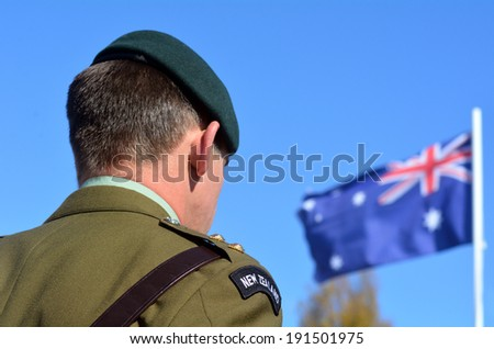 MANGONUI, NEW ZEALAND - APRIL 25 2014: New Zealand Army officer stands under New Zealand flag during the National War Memorial service. - stock photo
