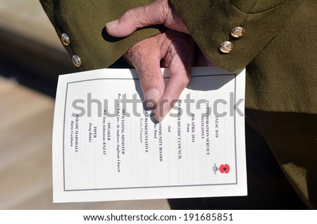 MANGONUI, NEW ZEALAND - APRIL 25 2014:New Zealand Army veteran soldier hands holds  ANZAC order of service during a National War Memorial Anzac Day in New Zealand. - stock photo
