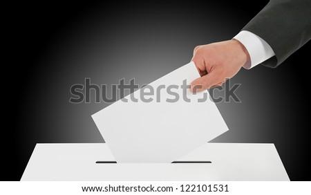 Manhand down ballot in the ballot box. Dark background. - stock photo