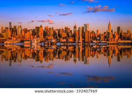 Manhattan at sunset reflected in the hudson river - stock photo