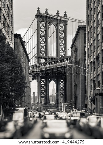 Manhattan Bridge and Empire State Building seen from Brooklyn, New York. Black and white image with a blurred foreground - stock photo