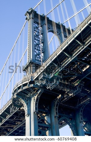 Manhattan Bridge tower showing intricate clear detail underneath with a clear blue sky