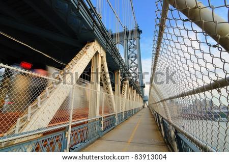 Manhattan Bridge Walkway in New York City as a train speeds by. - stock photo