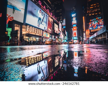 Manhattan, circa oct 2014: Typical Time square night view scenery in New york city. Taxi, lights and tourist are reflected in a  water puddle - stock photo