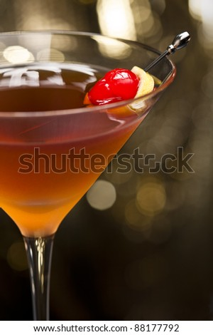 Manhattan cocktail garnished with a cherry and lemon and gold glitter back ground - stock photo