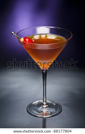 Manhattan cocktail garnished with a cherry and lemon with blue black back ground - stock photo