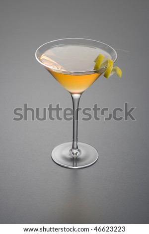 Manhattan cocktail with lemon peel garnish close up on grey background - stock photo