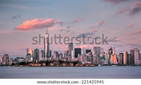 Manhattan financial district and Ellis Island at dusk. - stock photo