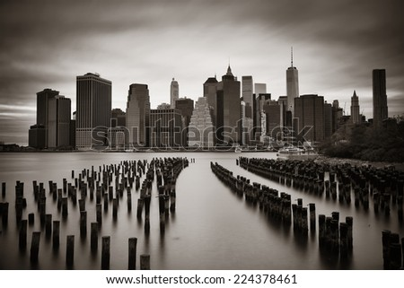 Manhattan financial district with skyscrapers and abandoned pier over East River in BW. - stock photo