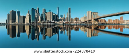 Manhattan financial district with skyscrapers and Brooklyn Bridge with reflections. - stock photo